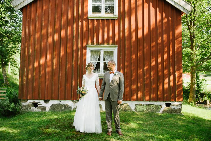 Bröllop Hyssna Gamla Kyrka - porträtt bröllopsfotograf brudpar vid husvägg