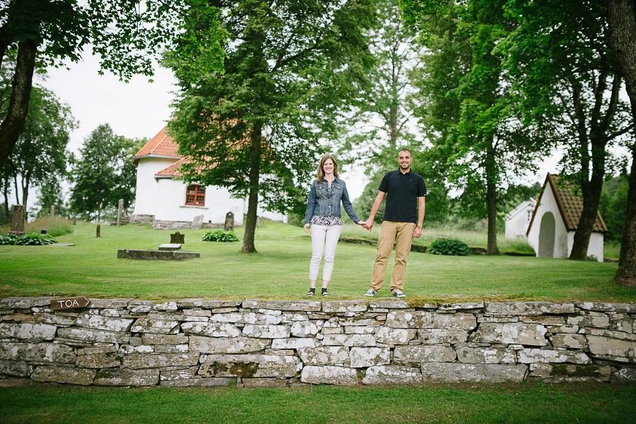 Emily och Firas provfotografering vid Hyssna Gamla Kyrka av bröllopsfotograf David Berg. Bröllopsparet står på muren.