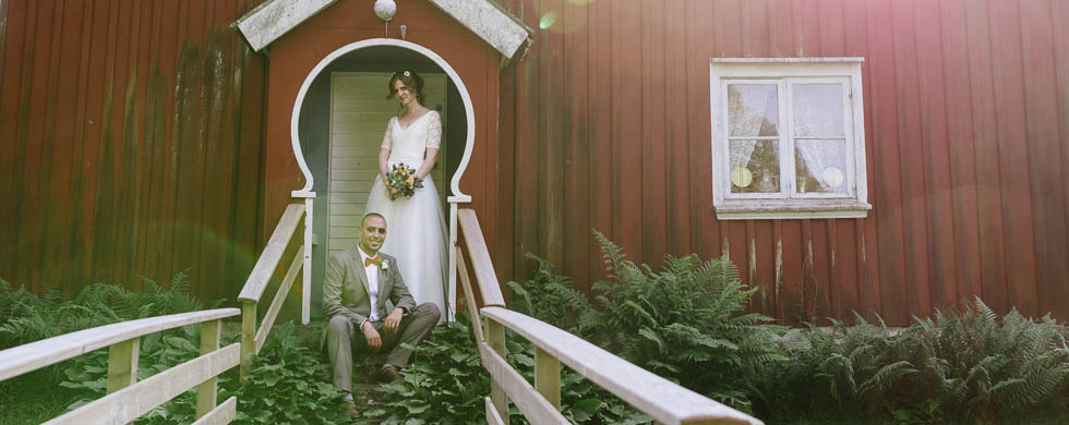 Bröllopsparet vid en dörrpost i motljus av bröllopsfotograf David Berg Hyssna