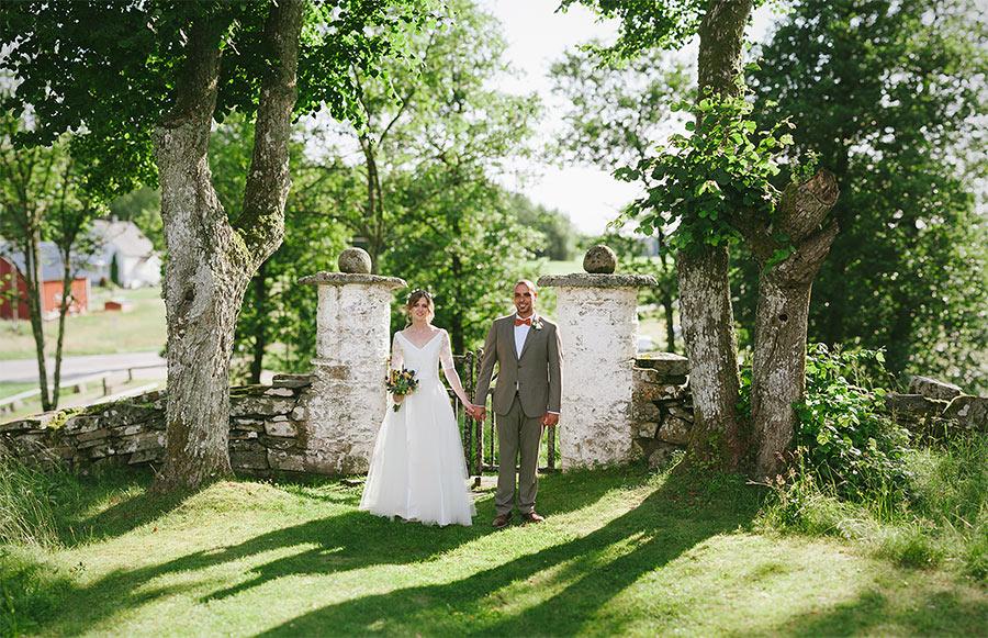 Bröllopsparet framför en grind vid Hyssna Gamla kyrka fotograferat av bröllopsfotograf Hyssna - David Berg