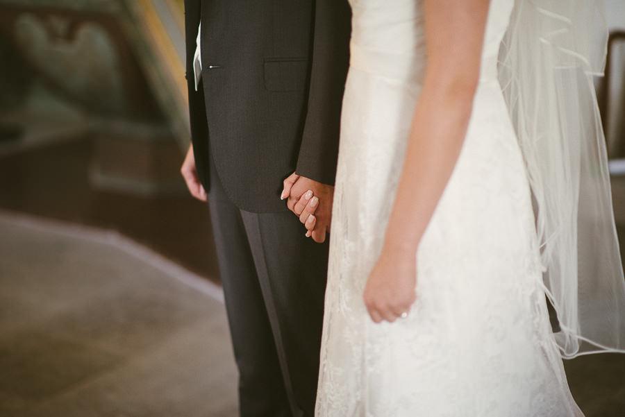 Bröllopsfotograf Tuve kyrka - Vigsel. Brudparet håller handen.