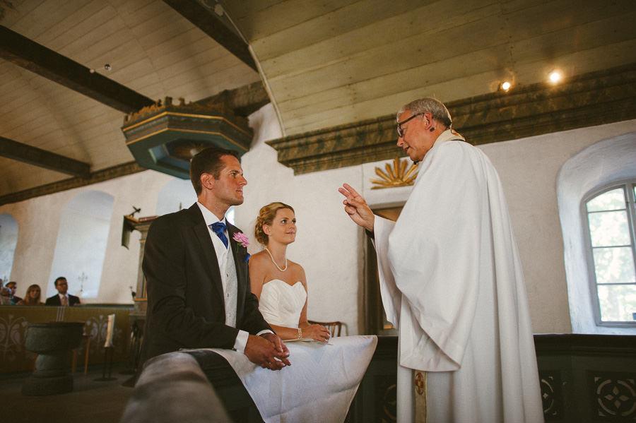 Bröllopsfoto Tuve kyrka - Vigsel. Brudparet på knä.
