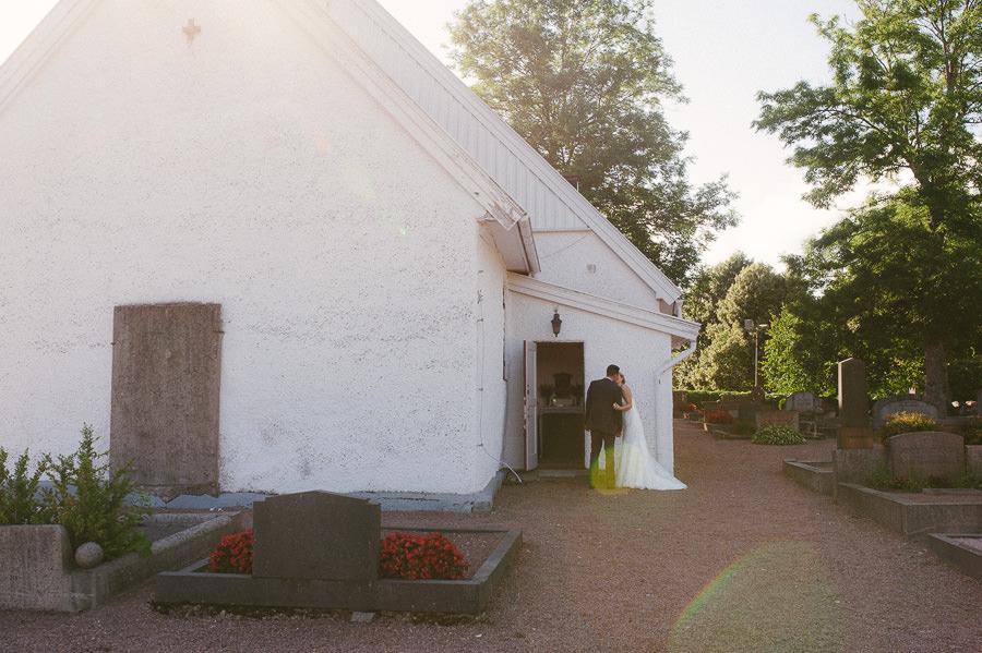 Bröllopsfotograf Hisingen. Tuve kyrka. Bröllopsparet gömmer sig.