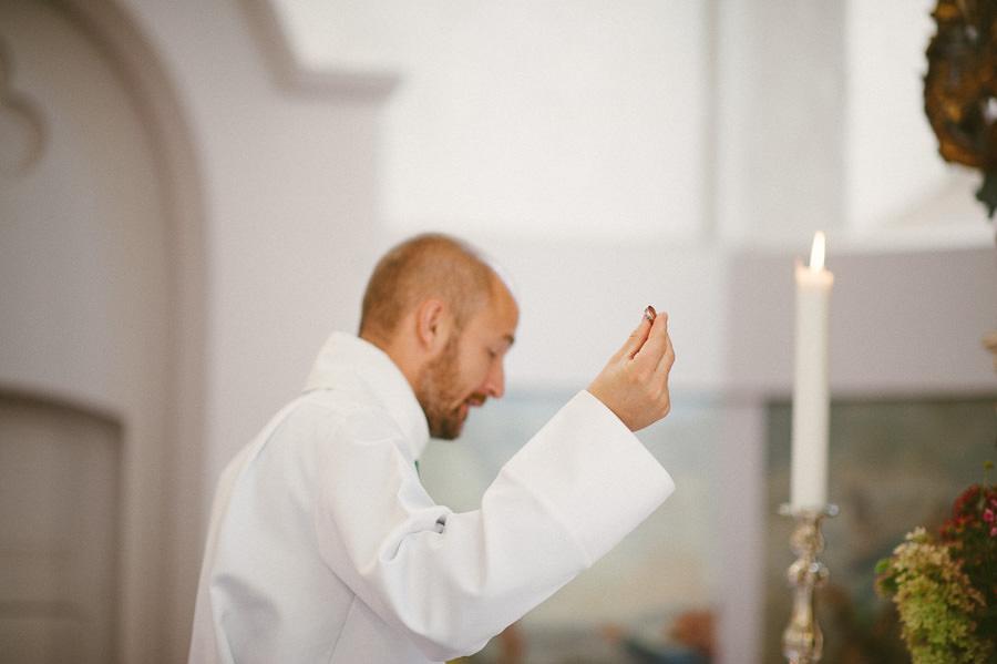 Bröllopsfotograf Mölndal. Bröllop i Fässbergs kyrka - prästen håller upp ringen under vigseln