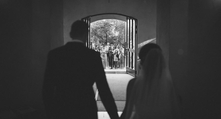 Bröllopsfotograf Mölndal fotojournalistisk reportagestil. Bröllop i Fässbergs kyrka - brudparet hand i hand till gratulationer