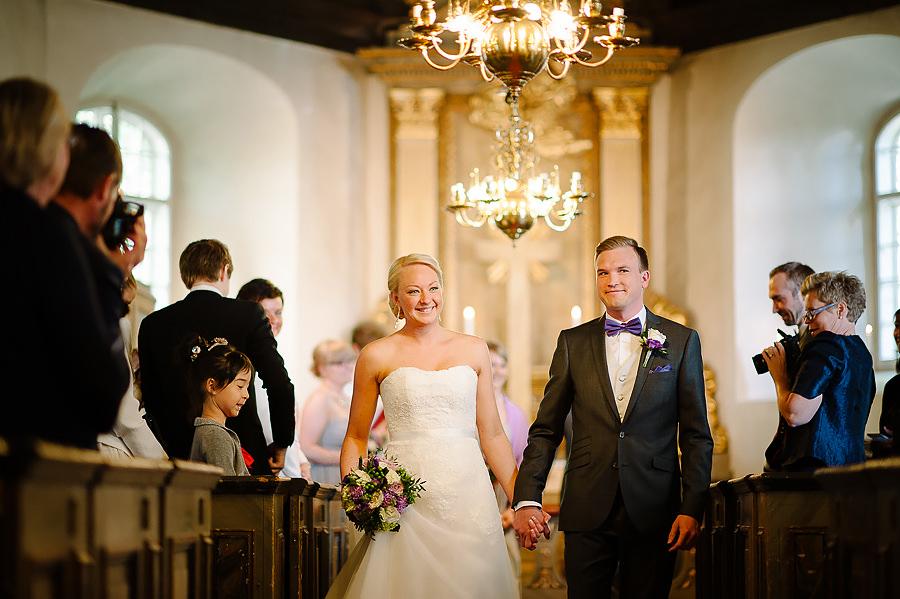 Vigsel i Örgryte Gamla Kyrka, brudparet på väg ut hand i hand