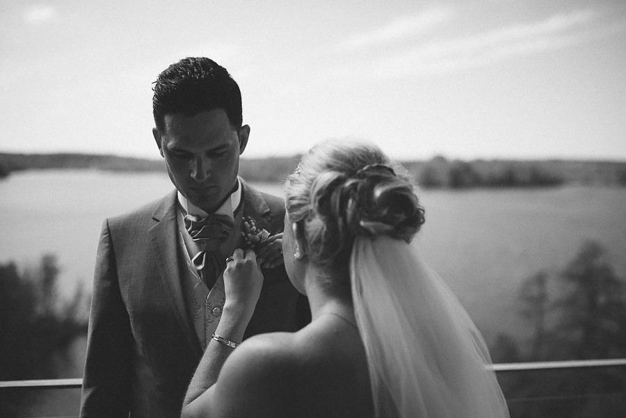 Bruden rättar till knappnålsblomman på brudgummen vid bröllop på Nääs Fabriker / Sjölyckan. Bröllopsfotograf David Berg.