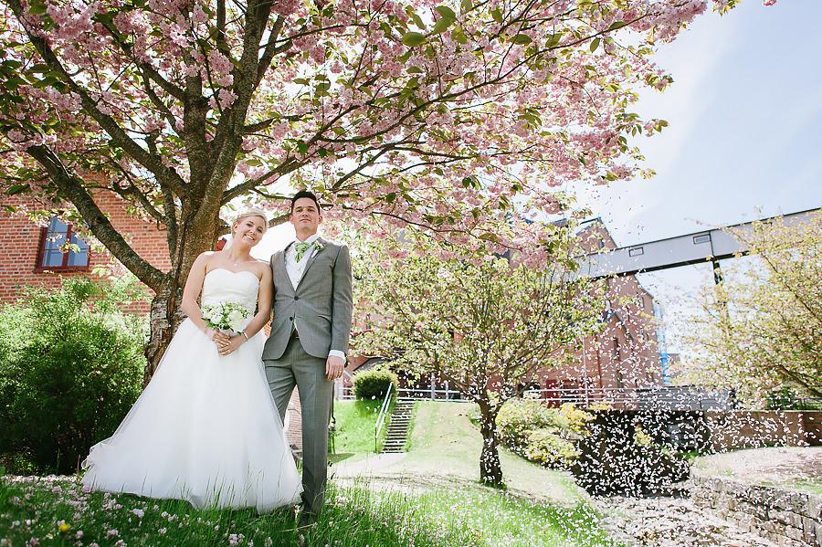 Brudparet under körsbärsträd vid Nääs Fabriker utanför Göteborg