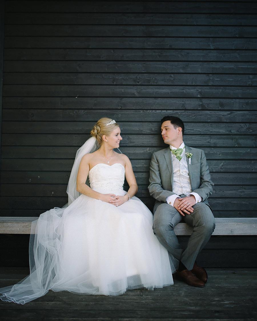 brudparet pustar ut efter porträttfotografering vid Nääs Fabriker