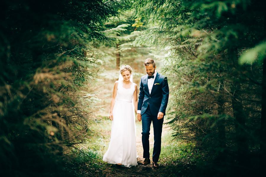 Skogsbröllop i trollskogen. Viared mellan Göteborg och Borås. Brudparet promenerar hand i hand.