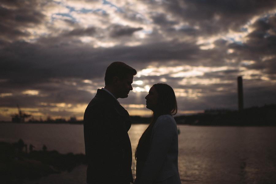 pre wedding fotografering vid Röda Sten - solnedgång över hamninloppet och brudparet i siluett