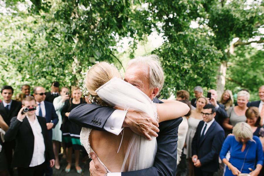 Gratulationer utanför Särö Kyrka. Brudparet på trappan med kram från brudens far