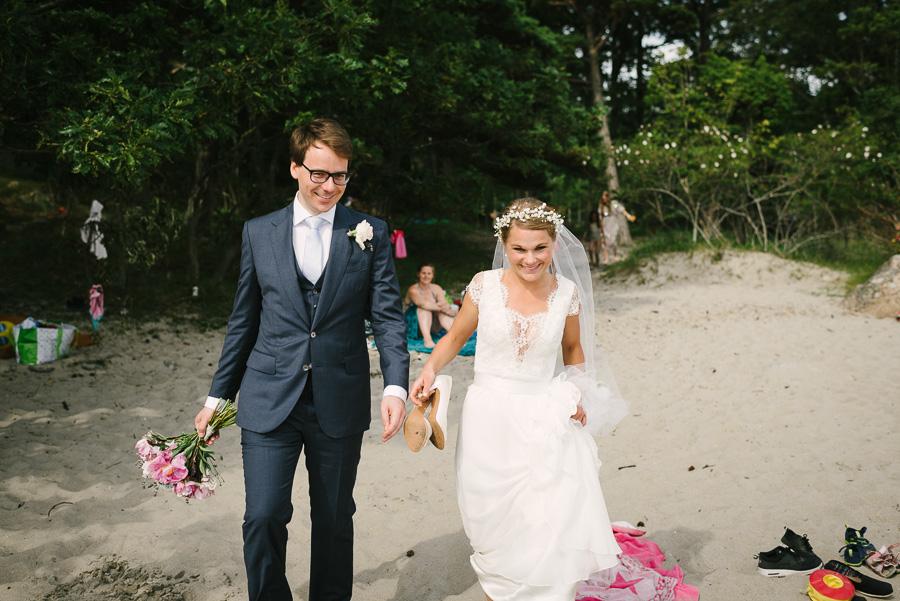 Sommarbröllop i juli. Särö Västerskog naturreservat. Brudparet promenerar på sandstranden